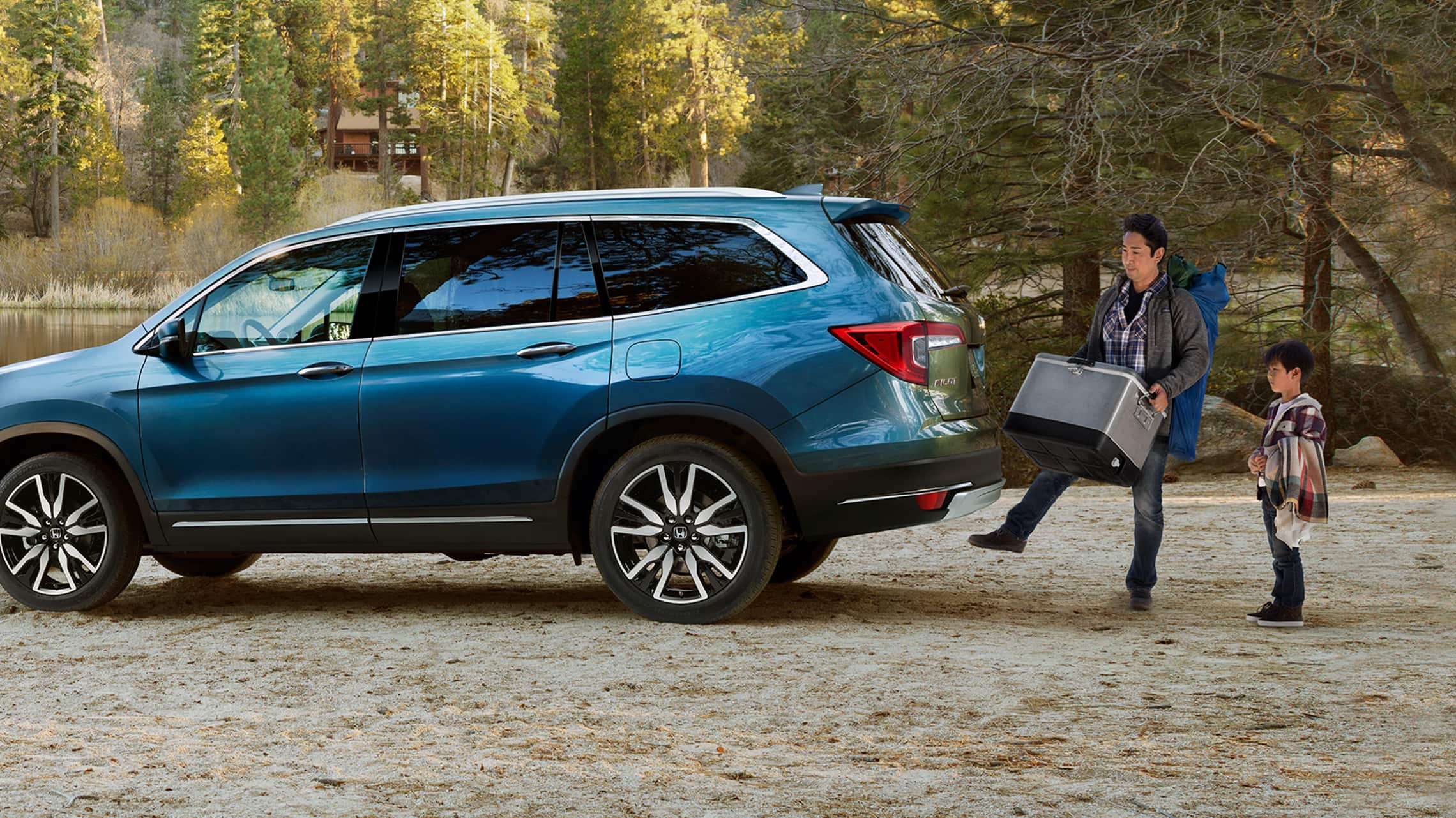 Driver's side profile view of 2021 Honda Pilot Elite in Steel Sapphire Metallic parked next to a lake displaying the hands-free access power tailgate.