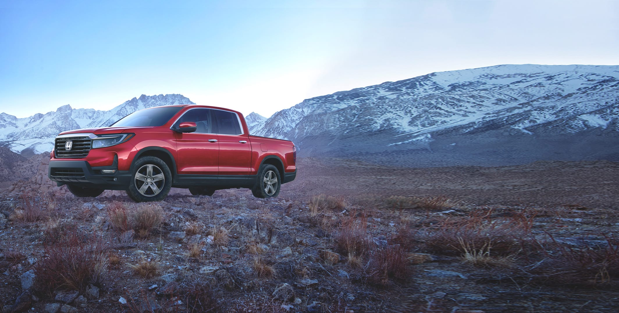 Driver-side view of the 2021 Honda Ridgeline RTL-E in Radiant Red Metallic II shown parked in a rugged, mountainous landscape.